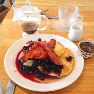 Fluffy buttermilk pancakes with streaky bacon, warmed blueberries and maple syrup